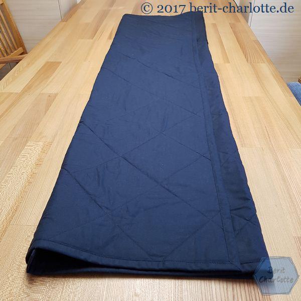 Den Quilt der Länge nach falten. Die Kissenplatte liegt unter der Decke zum Tisch hin.