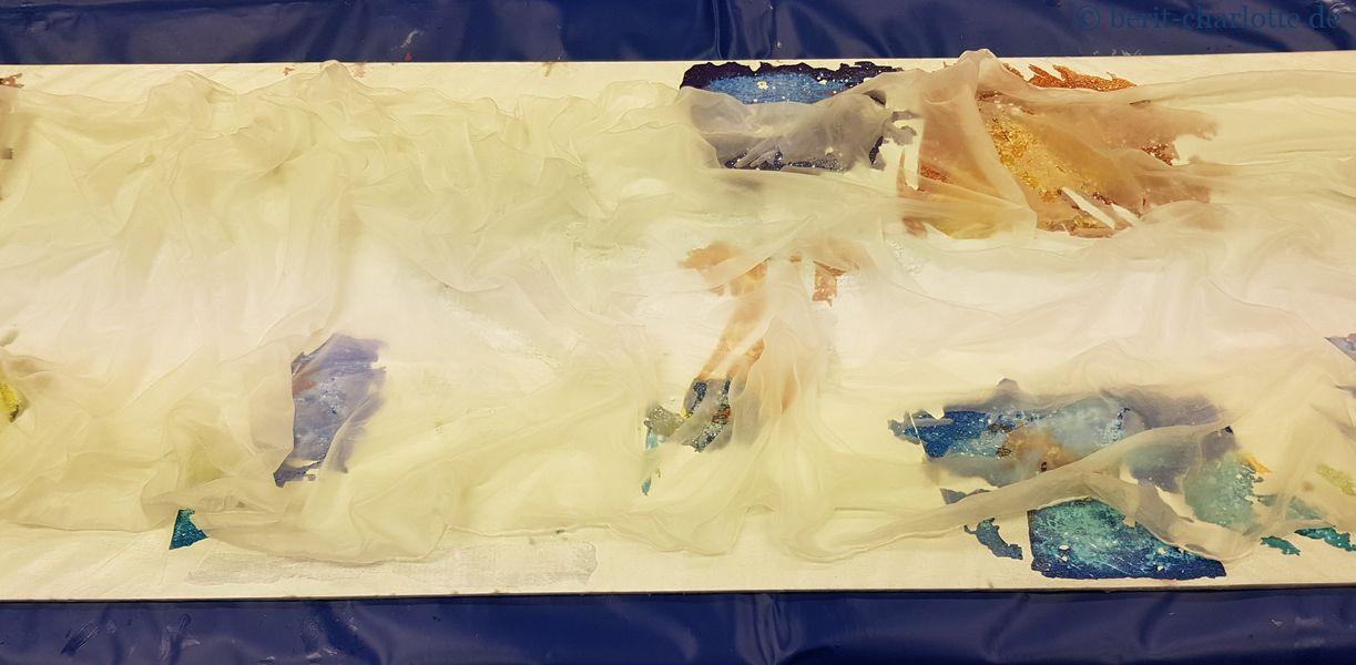 Tuch 1 - Wirbel gelegt (Stoff einfach fassen, hochziehen und drehen). Lasst euch nicht von den bunten Flecken irritieren, die Unterlagen sind mehrfach benutzt.