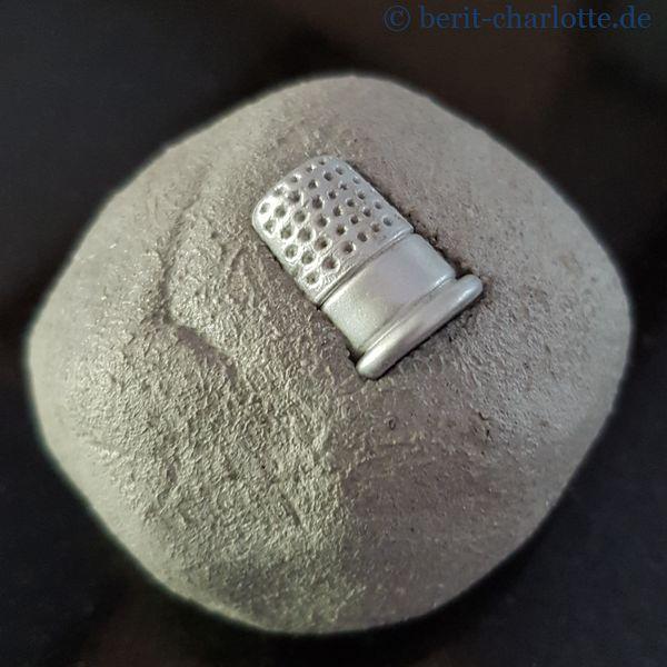 ... mit einem Fingerhut-Knopf ...