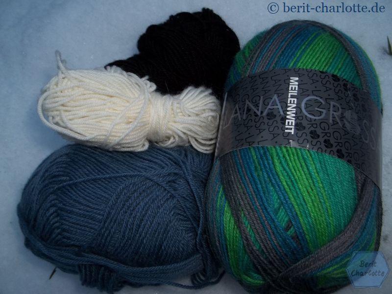 Die Wolle für die Socken mit dem Schaf: blau für den Himmel, weiß und schwarz für das Schaf und grün-braun für den Rest.